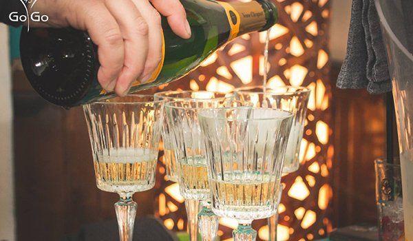una mano con una bottiglia che sta versando dello spumante dentro a dei bicchieri di cristallo