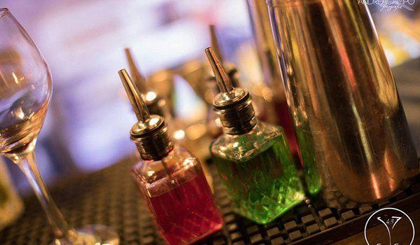 un calice di vetro, due boccette con dentro del liquido rosa e verde e sulla destra uno shaker in acciaio
