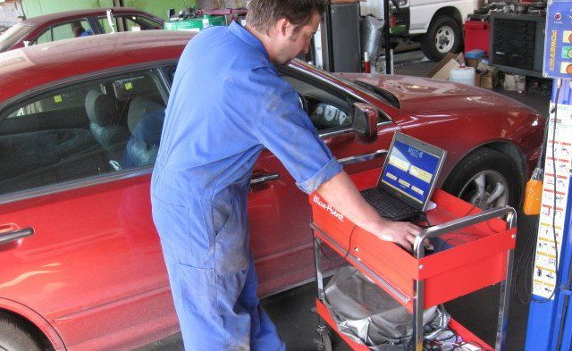 A mechanic as part of an auto technicians team looking at a damaged car in the Ruapehu District