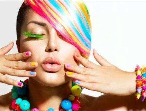 Una donna con capelli tinti multicolore e con degli accessori multicolore