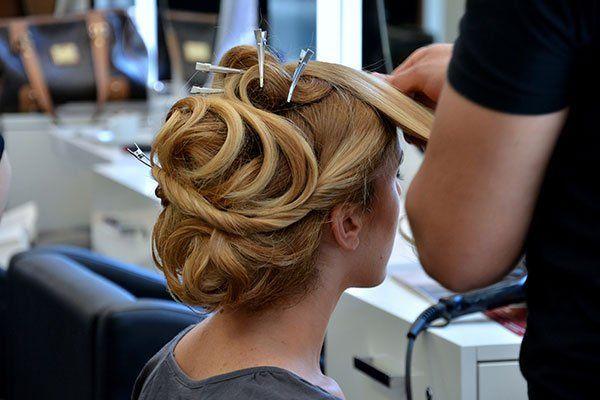 Un parrucchiere mentre fa un piega a una donna con capelli biondi