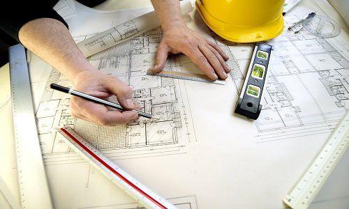 due mani che disegnano un progetto edile