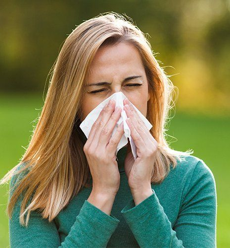 Woman with allergy blowing nose
