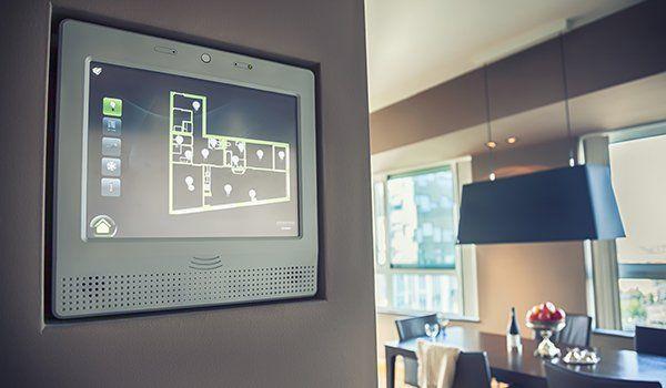 all'interno di un appartamento uno schermo con la piantina dell'appartamento e sulla destra un tavolo con sopra una lampada a sospensione