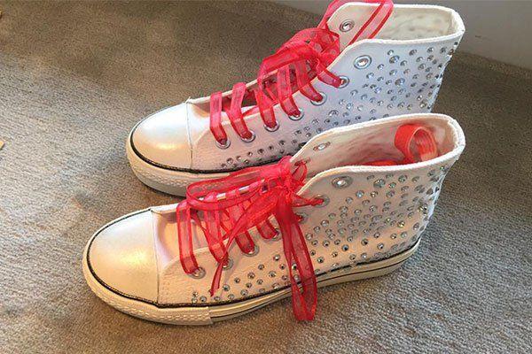 Scarpe sportive bianche ,con pietre incrustadas e chiuse con un nastro rosa brillante