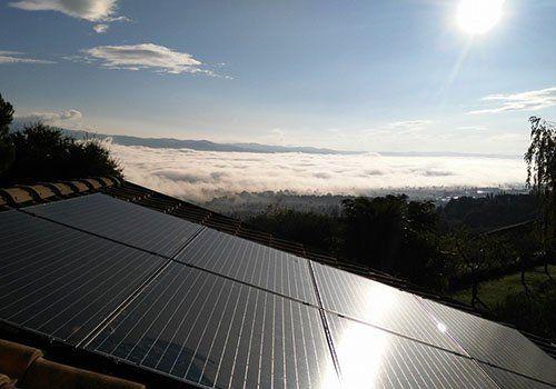 Vista di un tetto coperto di pannelli solari e al fondo un mare di nuvole