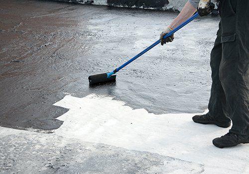 Roofer lavoratore dipingere il pennello a rullo, per l'impermeabilizzazione