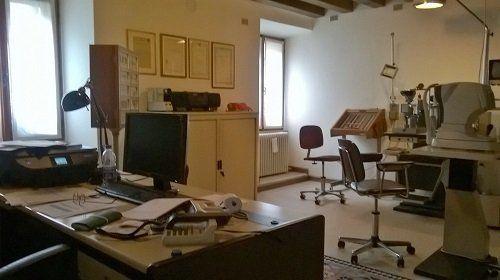 una scrivania con un monitor e dei macchinari in un laboratorio ottico