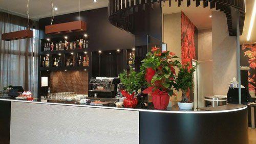 Interno di un ristorante e vista dell'angolo bar con dei vasi di fiori, macchina di caffè e liquori dietro