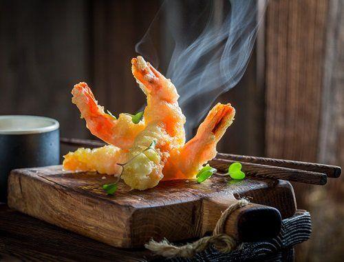 Dei gamberi in tempura su un tagliere tradizionale orientale