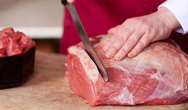 Un uomo mentre taglia un trancio di carne in fette con un coltello