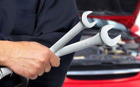 un meccanico con due chiavi inglesi in mano