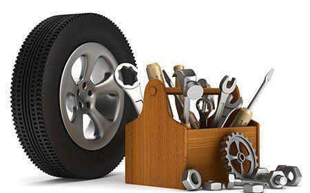 una cassetta di legno con degli attrezzi e una ruota