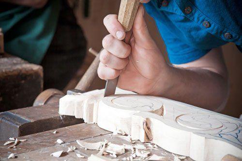 artigiano all'opera con uno scalpello su una decorazione di legno