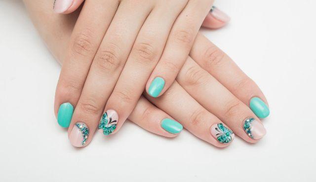 Manicure, unghie di vari colori, ornamenti di pietre e di farfalle