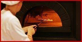 pizzaiolo mentre inforna una pizza