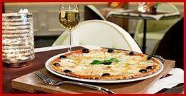 pizza nel piatto servita a tavola con calice di vino
