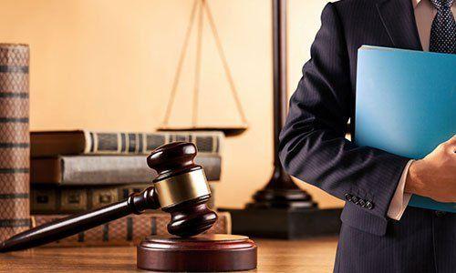 Uomo con una cartella, maza di giustizia e libri