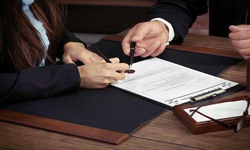 un cliente col suo avvocato che firmano fogli