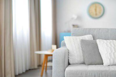 un divano grigio chiaro con tre cuscini appoggiati sul lato sinistro