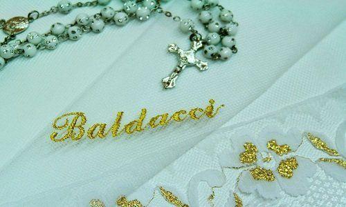 un tessuto in pizzo con scritto Baldacci e un rosario