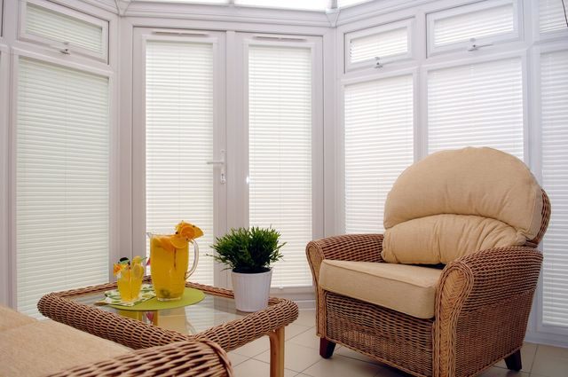 white blinds in a conservatory with furniture