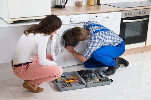 un tecnico mentre ripara una lavatrice e accanto una donna