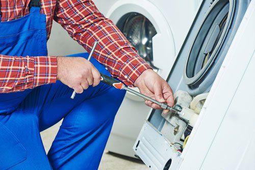 un tecnico mentre ripara una lavatrice