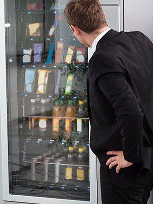 un uomo davanti a un distributore automatico