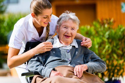 Professional caregiver taking care of the elderly lady