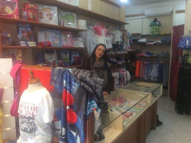una ragazza dietro al bancone di un negozio di vestiti