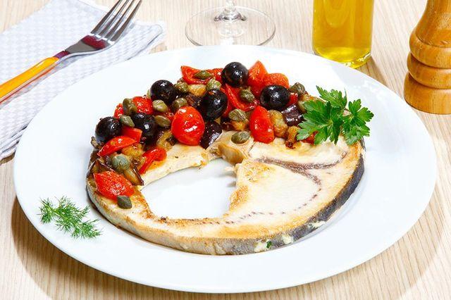 un trancio di pesce spada alla griglia con olive , capperi e pomodorini - milano