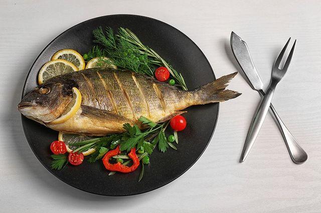 Un piatto con un pesce con dei tagli e aromi pronto per essere grigliata