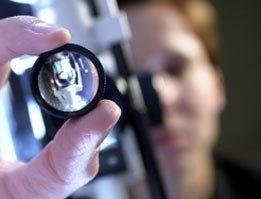 Due dita che tengono una lente per le analisi oculistiche