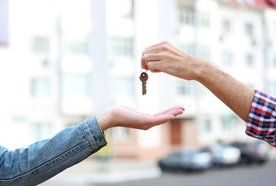 A set of keys being handed to another person