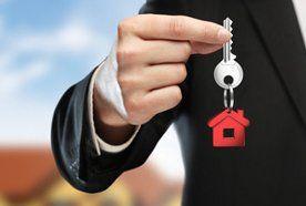 A man holding a set of keys with a house shaped key-chain