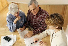 A mature couple looking through a legal document with their solicitor