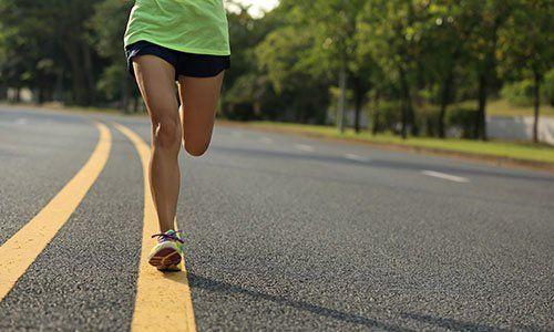 Le gambe di donna che corre su una strada
