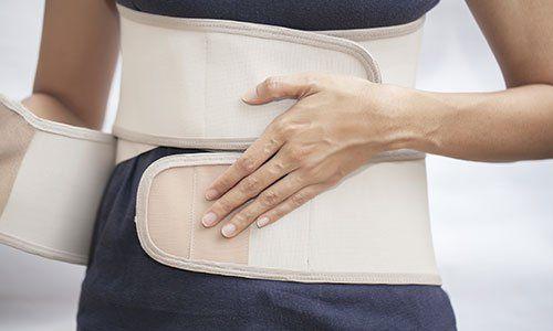 Donna che indossa una fascia di supporto muscolare per addome
