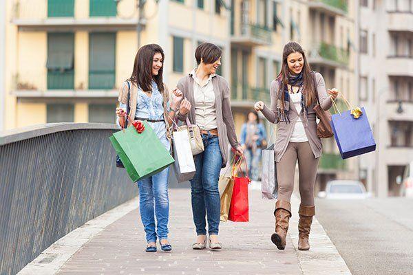 Tre belle donne giovani con borse della spesa