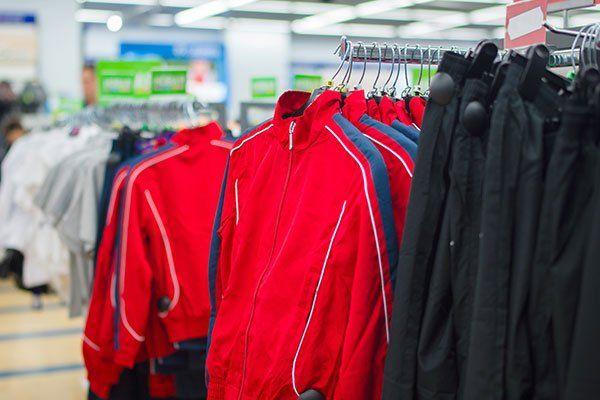 giacche sportive rosse e pantaloni in stand in supermercato