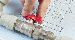 Primo piano di mani che aprono il rubinetto di una valvola su un disegno di una casa