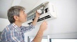 Operaio monta un condizionatore a soffitto