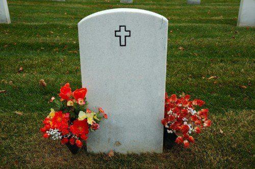 Lapida bianca con una croce nera e di fiori ai lati