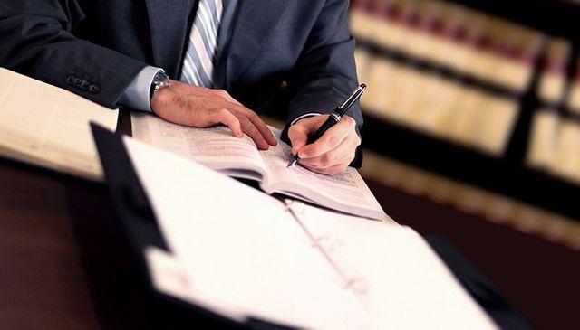 una persona seduta alla scrivania mentre scrive su un libro e sopra c'è un libro aperto