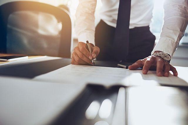 un uomo in piedi con le braccia appoggiate a una scrivania mentre scrive su un foglio