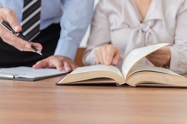 due persone a una scrivania, una è seduta che indica una pagina di un libro aperto e l'altra è in piedi con una penna in mano