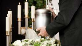 un uomo con una urna in mano e vista delle candele accese