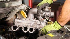 mani di un operaio con i guanti che assicurano una riparazione meccanica