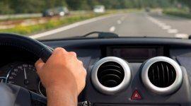 mano che tiene un volante alla guida